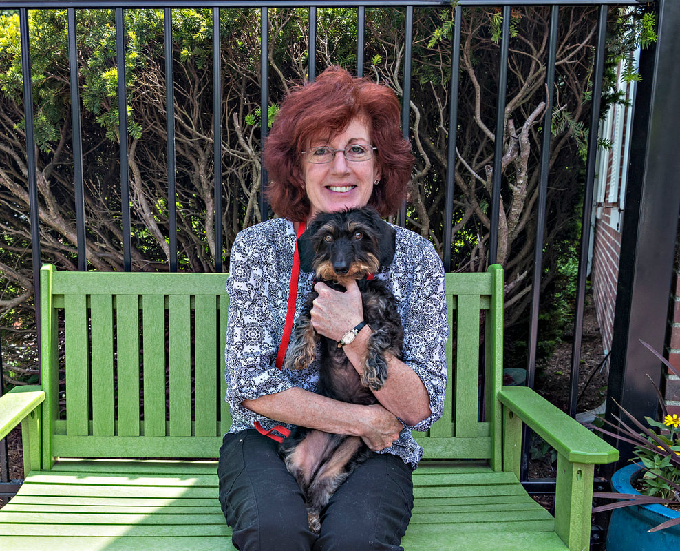 Photo of a woman with red hair holding a black and brown long haired Dachshund breed dog sitting on a green bench