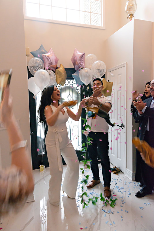 picture of a pregnant woman and her husband standing in an airy light-filled foyer in between bouquets of balloons popping a golden balloon filled with pink confetti, revealing the gender of their upcoming baby.