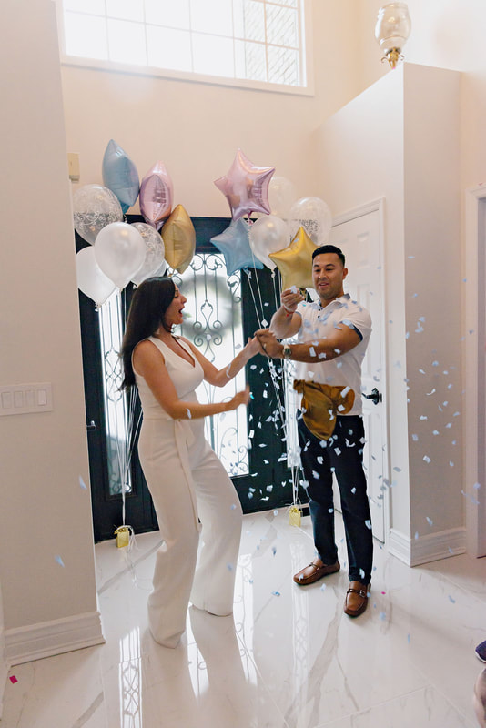 picture of a pregnant woman and her husband standing in an airy light-filled foyer in between bouquets of balloons popping a golden balloon filled with blue confetti, revealing the gender of their upcoming baby